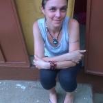 Seduta sulla soglia di casa a salutare e parlare con chi passa